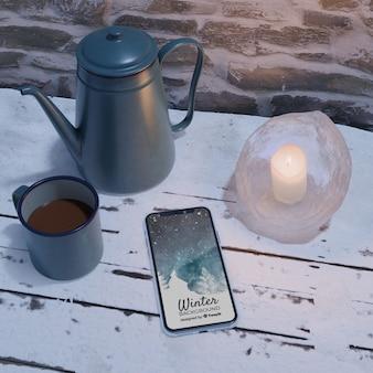 Dispositivo eletrônico ao lado da chaleira com chá