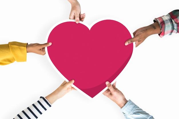 Diversas mãos segurando um coração vermelho