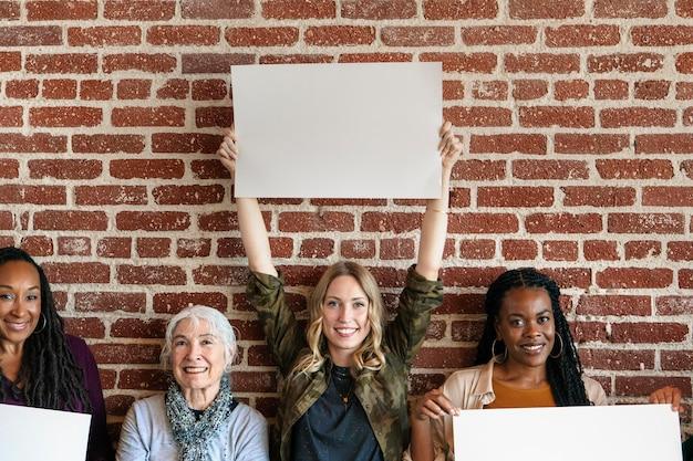 Diversas mulheres exibindo modelo de pôsteres em branco