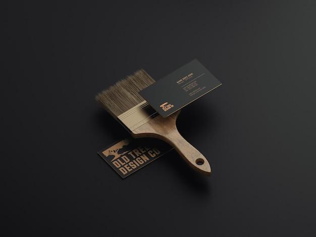 Dois cartões de visita flutuando com um pincel com marca de papelaria mockup vista em perspectiva