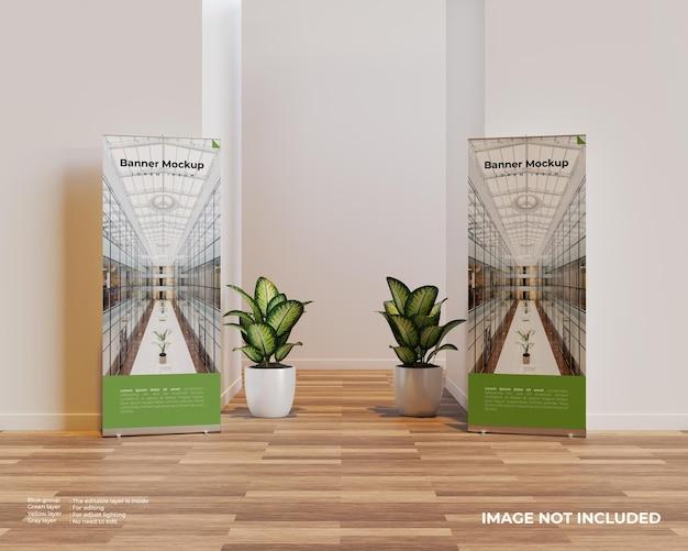 Dois enrolam maquete de banner em cena interior com duas plantas