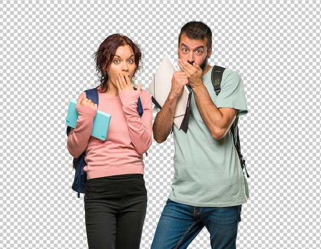 Dois estudantes com mochilas e livros cobrindo a boca para dizer algo inadequado. não posso falar