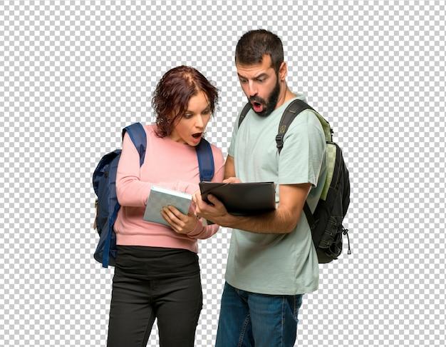 Dois, estudantes, com, mochilas, e, livros, lendo um livro