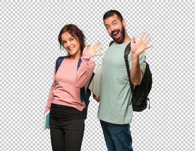 Dois, estudantes, com, mochilas, e, livros, saudando, com, mão, com, feliz, expressão