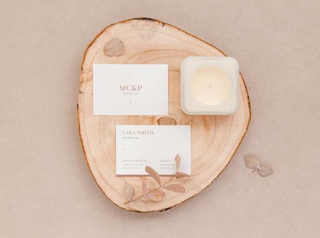 Duas elegantes maquetes de cartão de visita, folhas e velas em um baú em estilo plano