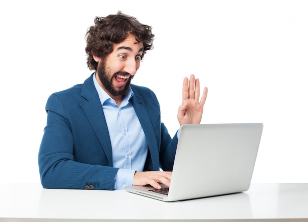 Empregado alegre que trabalha com seu portátil
