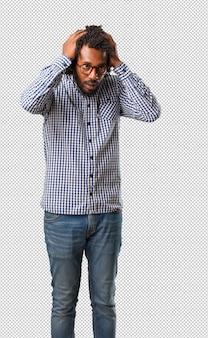 Empresário americano africano bonito frustrado e desesperado, irritado e triste com as mãos na cabeça