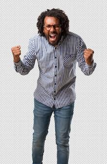 Empresário americano africano bonito gritando com raiva, expressão de loucura e instabilidade mental, boca aberta e olhos entreabertos, conceito de loucura