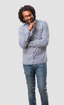 Empresário americano africano bonito pensando e olhando para cima, confuso sobre uma idéia, estaria tentando encontrar uma solução