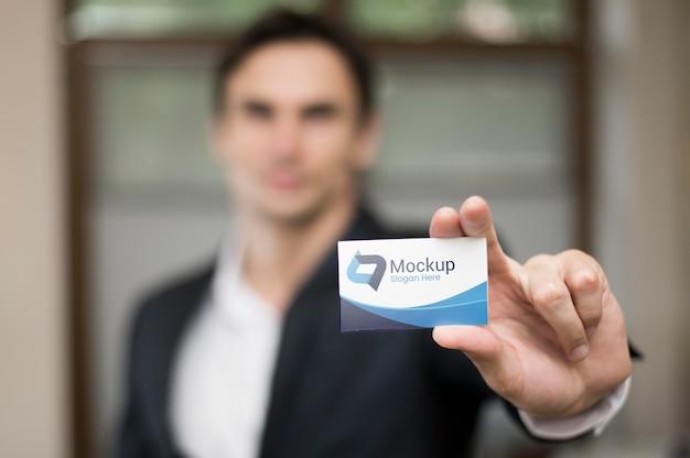 Empresário desfocado segurando um cartão de visita