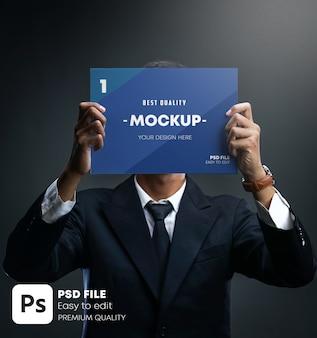 Empresário segurando cartaz com design de folheto cobrindo o rosto