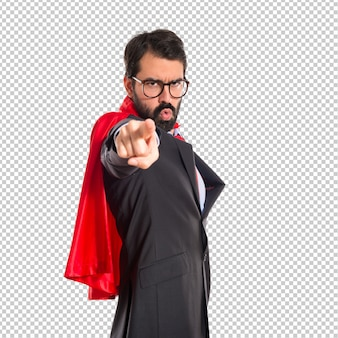 Empresário vestido de super-herói, apontando para a frente