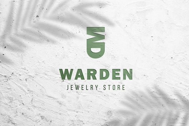 Entalhe a maquete do logotipo 3d na parede de concreto branca.