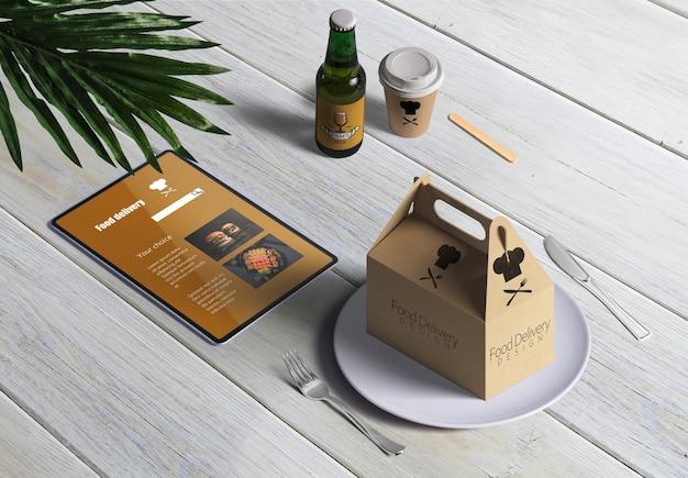Entrega de comida com caixa de papelão e menu na mesa de madeira