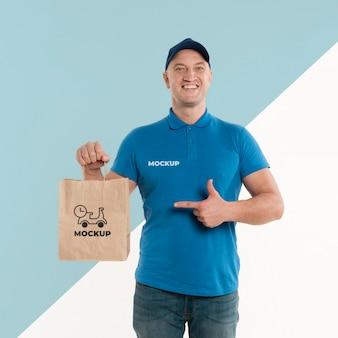 Entregador apontando para uma sacola de compras