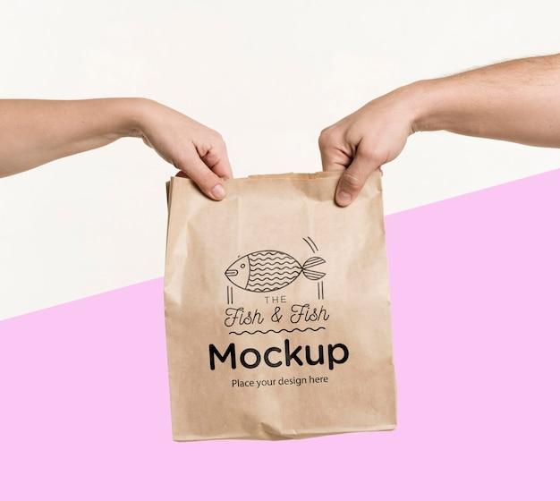 Entregador entregando uma sacola de comida para um cliente com maquete