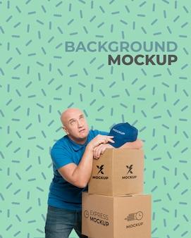 Entregador parecendo cansado ao lado de um monte de caixas com modelo de fundo
