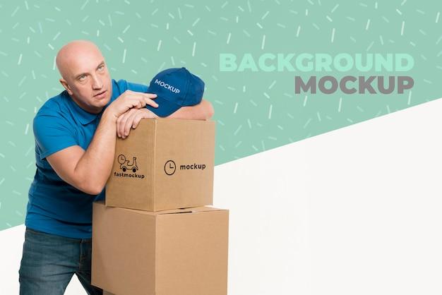 Entregador parecendo cansado ao lado de um monte de caixas
