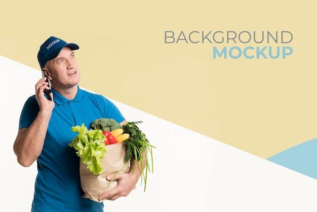 Entregador preocupado segurando uma caixa com vegetais diferentes