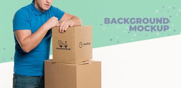 Entregador se apoiando em um monte de caixas com maquete de fundo