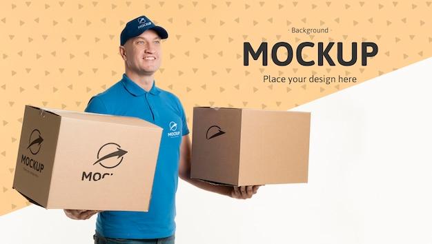 Entregador segurando caixas com modelo de fundo