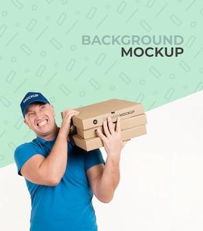 Entregador segurando caixas com pizza e maquete de fundo