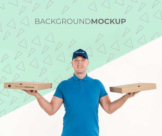 Entregador segurando caixas de pizza com maquete de fundo
