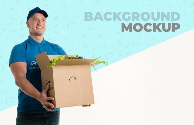 Entregador segurando uma caixa cheia de vegetais