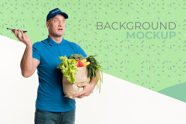 Entregador segurando uma caixa com diferentes vegetais e uma maquete de fundo