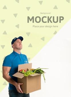 Entregador segurando uma caixa com vários vegetais