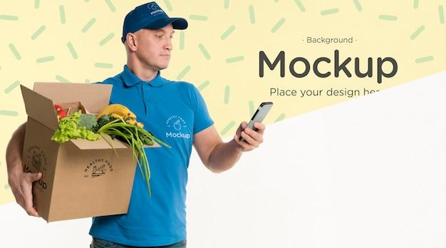 Entregador segurando uma caixa de legumes com uma maquete de fundo
