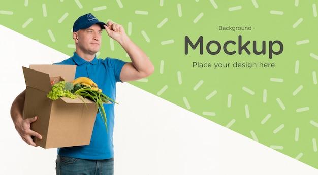 Entregador segurando uma caixa de legumes