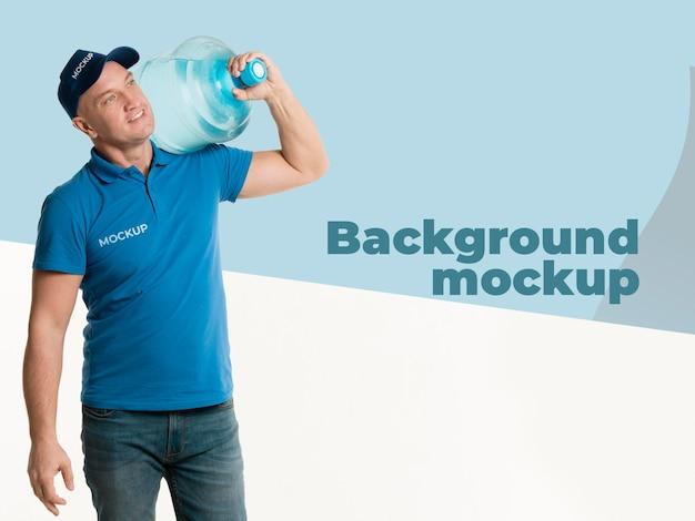 Entregador segurando uma garrafa de água com maquete de fundo