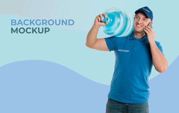 Entregador segurando uma garrafa grande de água enquanto fala ao telefone