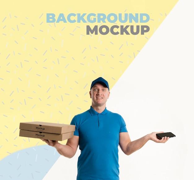 Entregador segurando uma maquete de caixas de pizza com maquete de fundo