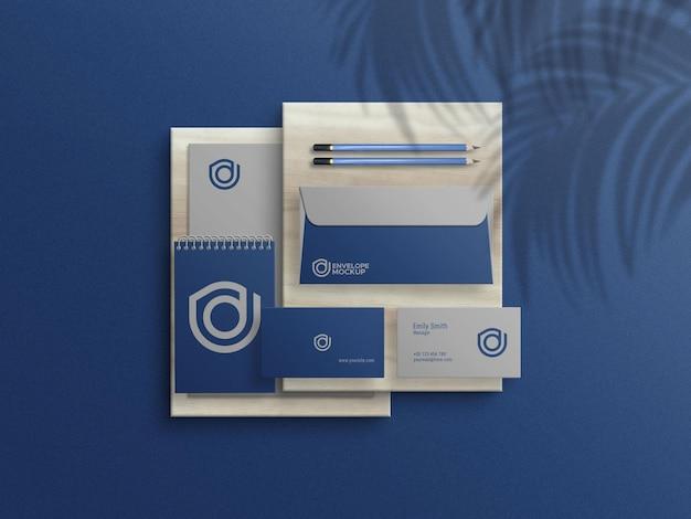 Envelope com cartão de visita e bloco de notas timbrado em textura de madeira