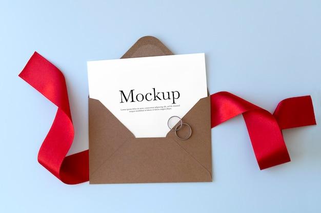 Envelope com fita vermelha e maquete de anéis