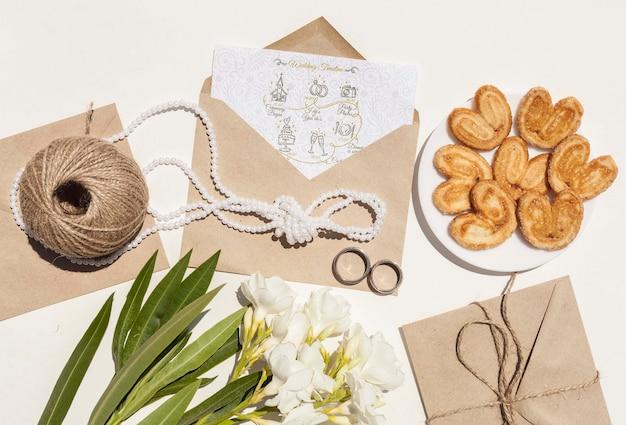 Envelope de papel com flores e biscoitos de casamento