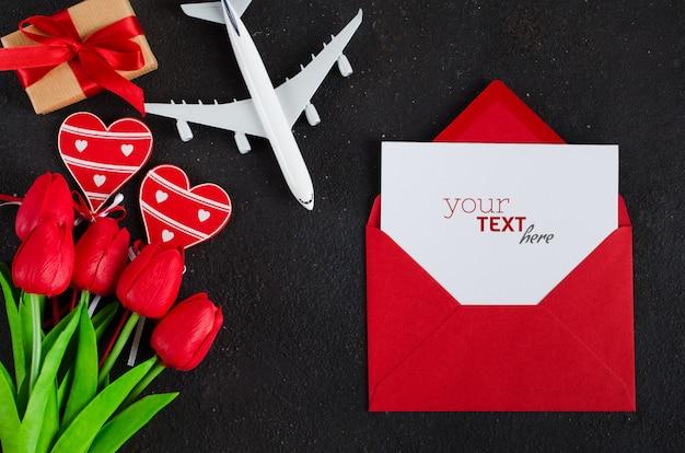 Envelope vermelho com papel em branco, modelo de avião, buquê de tulipas e caixa de presente com corações