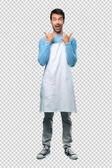 Equipe vestir uma doação do avental os polegares acima do gesto com ambas as mãos e sorriso. expressão alegre