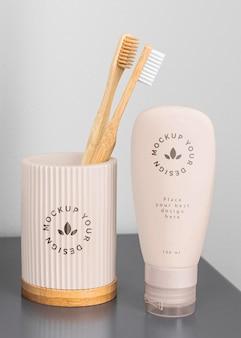 Escovas de dente em copo e recipiente de creme