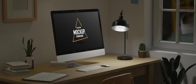 Escritório em casa à meia-noite monitor de computador em branco sob luz fraca do espaço de trabalho escuro da lâmpada