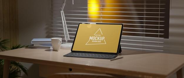 Espaço de trabalho à noite tela vazia do tablet sob a luz da lâmpada nas cortinas de madeira da janela