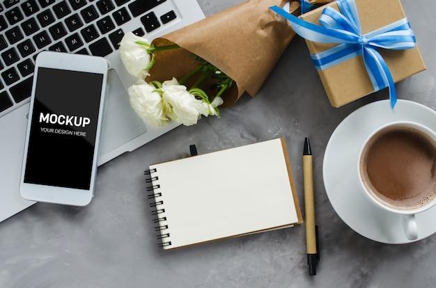 Espaço de trabalho com computador portátil, tela de smartphone simulado acima, caixa de presente e café.