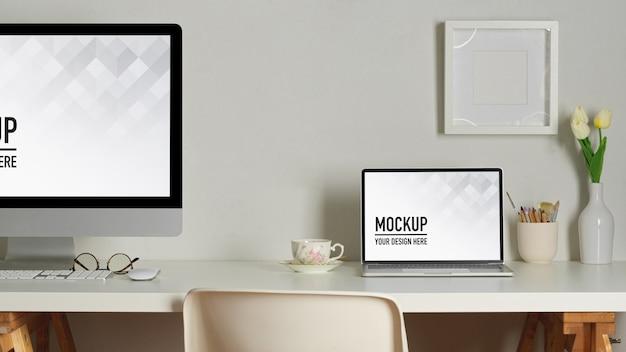 Espaço de trabalho com maquete de laptop e desktop, livros e artigos de papelaria