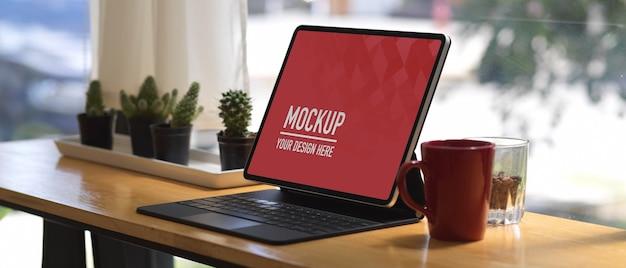 Espaço de trabalho com tablet digital com maquete de teclado e caneca