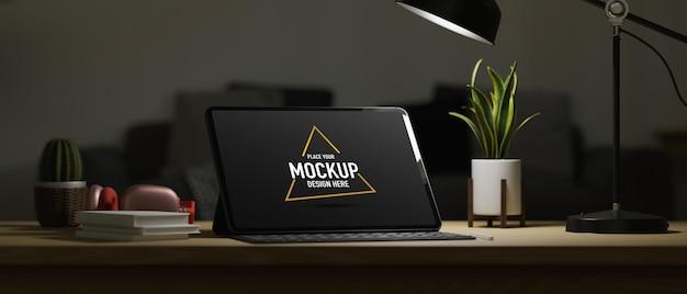 Espaço de trabalho com tela em branco, livros de lâmpadas para tablets inteligentes e itens de decoração à meia-noite, trabalho à noite