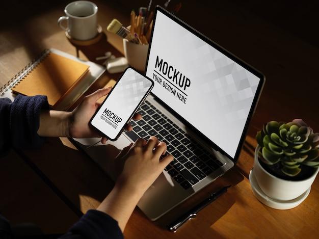 Espaço de trabalho com telefone digital e maquete de laptop com caneca