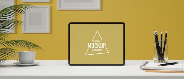 Espaço de trabalho criativo na tela do tablet vazio de parede amarela na mesa branca e moldura em branco na parede