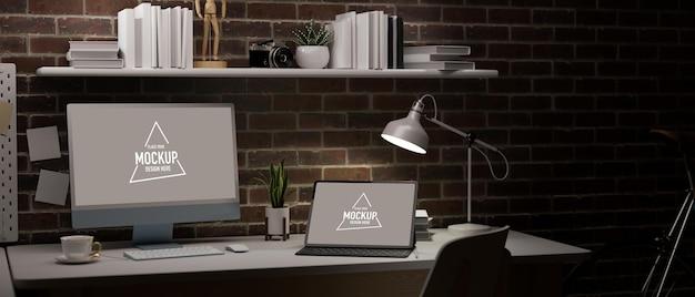 Espaço de trabalho escuro em apartamento com parede de tijolo vermelho, laptop em branco e tela de tablet para sua marca